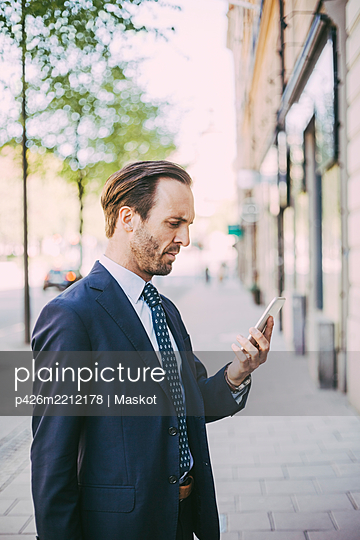 Side view of businessman using phone in city - p426m2212178 by Maskot