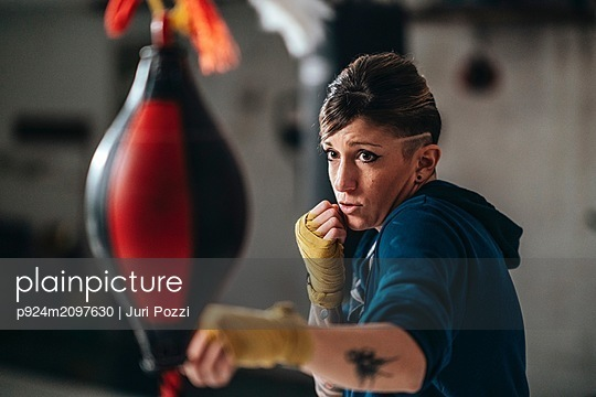 Boxer training with punch bag in gym - p924m2097630 by Juri Pozzi