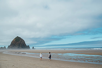 Rear view of girls walking on shore at beach against cloudy sky - p1166m1524541 by Cavan Images