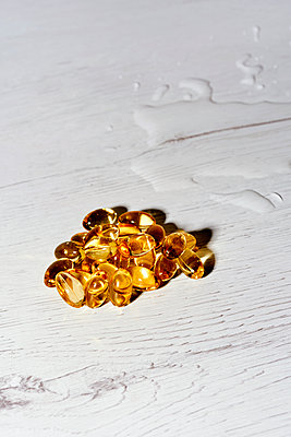 Omega-3 fatty acid nutritional supplement capsules and some water spilled on a white wooden table - p1423m2245758 by JUAN MOYANO