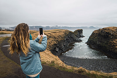 Iceland, back view of young woman taking picture with smartphone at coast - p300m2005552 von Kike Arnaiz