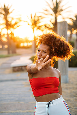 Young happy woman expressing V gesture with fingers - p300m2144187 by Manu Padilla Photo