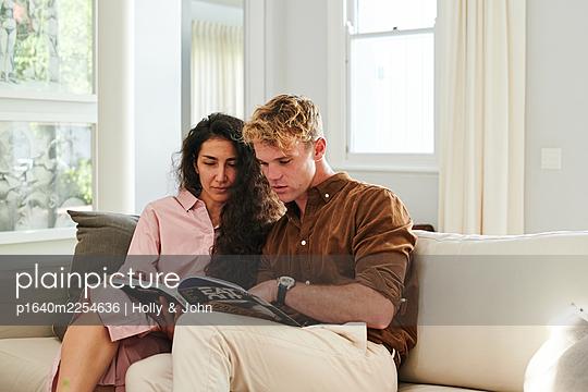 Paar auf der Couch betrachtet ein Magazin - p1640m2254636 von Holly & John