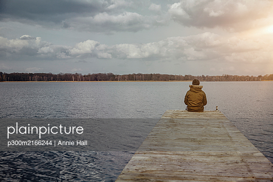 Back view of young man sitting on a jetty looking at lake in winter - p300m2166244 by Annie Hall