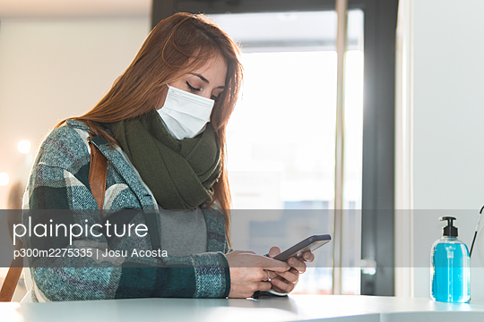 Portrait of young woman wearing protective face mask waiting in beauty salon lobby with smart phone in hands - p300m2275335 by Josu Acosta
