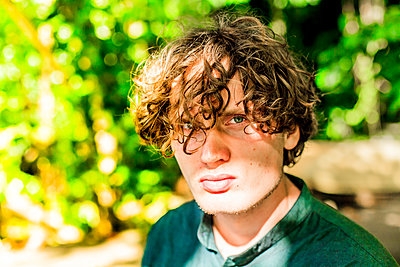 Young man with curly hair - p075m2071225 by Lukasz Chrobok