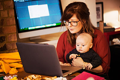 A woman seated with a baby on her lap, using a computer laptop, both people looking intently at the screen.  - p1100m1425071 by Mint Images