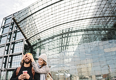 Happy young woman surprising boyfriend at the central station, Berlin, Germany - p300m2154547 by Hernandez and Sorokina