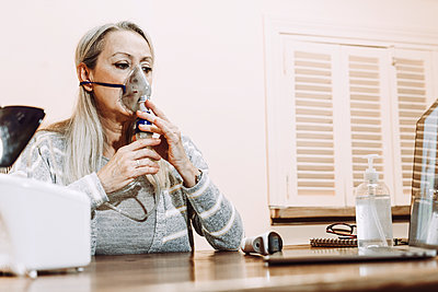 Senior woman using nebulizer during online consultation doctor at home - p300m2240412 by Eloisa Ramos