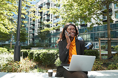 Smiling businesswoman with laptop talking on phone at office park - p300m2241035 by Pete Muller