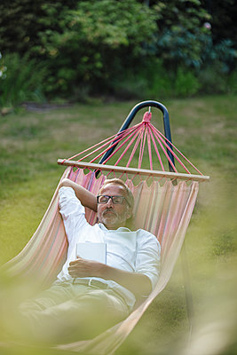 Mature man with book relaxing on hammock in backyard - p300m2277027 by Gustafsson