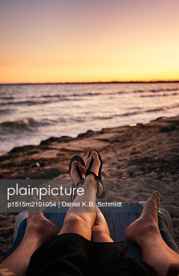 Couple relaxing together on a single beach chair during sunset - p1515m2101054 by Daniel K.B. Schmidt