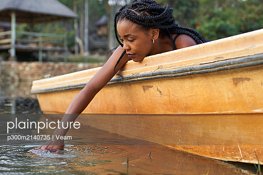 Young woman in a boat holding her hand into the water - p300m2140735 by Veam