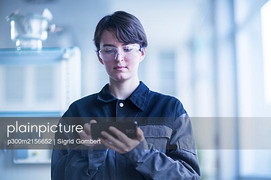 Female technician using smartphone - p300m2156652 by Sigrid Gombert