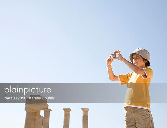 Boy taking photo at historical ruins