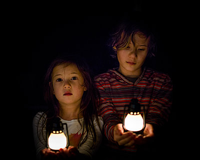 Two small children stand in dark with small lanterns in their hands - p1166m2094453 by Cavan Images