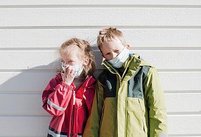 siblings wearing medical masks to protect from corona virus - p1166m2171491 by Cavan Images