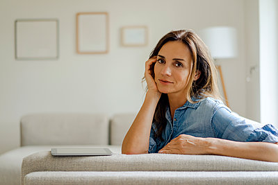 Portrait of mature woman resting on couch at home - p300m2029910 von Kniel Synnatzschke