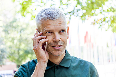 Portrait of mature man on cell phone outdoors - p300m2030414 von Tom Chance