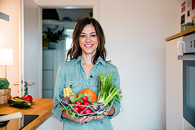 Woman standing in kitchen, holding basket full of fresh fruit and vegetables - p300m2069726 von Robijn Page