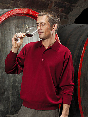 A vintner tasting a red wine - p3018500f by Paul Hudson