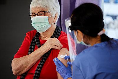 Senior woman getting covid vaccine - p312m2249667 by Plattform