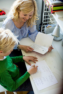 High angle view of mother helping son with homework at table - p426m844598f by Maskot