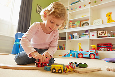 Female toddler playing with toy train on playroom floor - p429m1408252 by Emma Kim