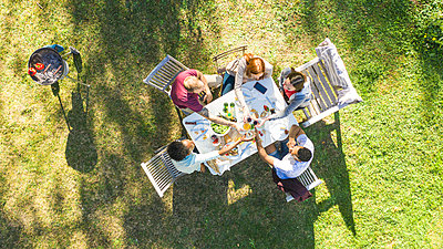 Happy young friends toasting beer bottles in garden - p623m2294753 by Gabriel Sanchez