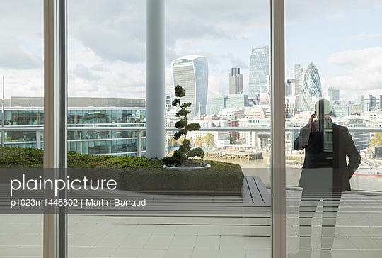 Businessman talking on cell phone on balcony with urban city view, London, UK - p1023m1448802 by Martin Barraud