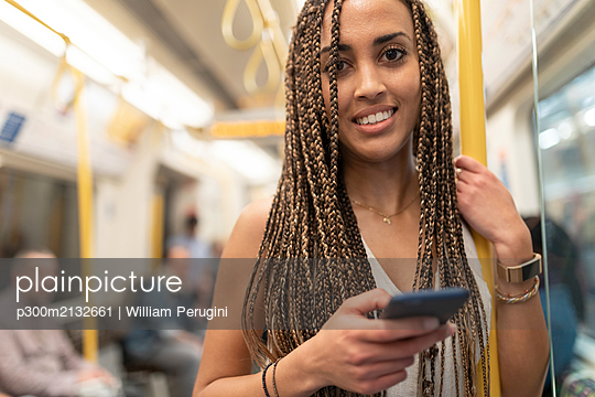 Portrait of smiling young woman with cell phone in underground train, London, UK - p300m2132661 by William Perugini