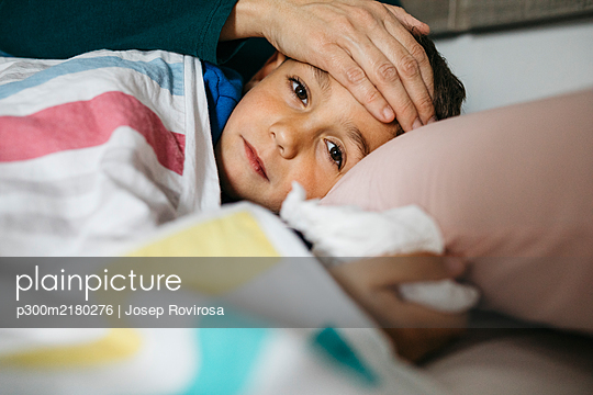 Portrait of sick boy lying in bed while his mother touching his forehead - p300m2180276 by Josep Rovirosa