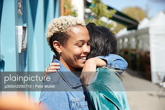Lesbian couple embracing each other on sunny day - p300m2290710 by Pete Muller