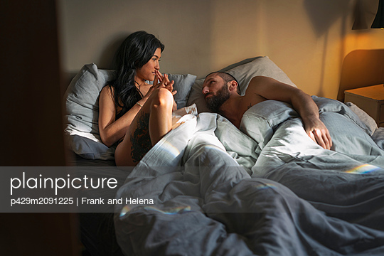 Hipster couple resting in bed - p429m2091225 by Frank and Helena