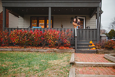 distant view of mother holding small child standing on front porch - p1166m2112949 by Cavan Images