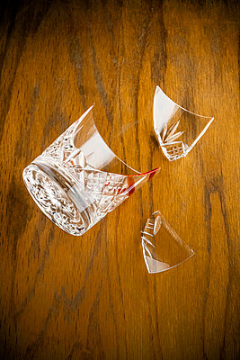 Broken and bloody cut glass whiskey tumbler on a wooden surface - p1302m2141485 by Richard Nixon