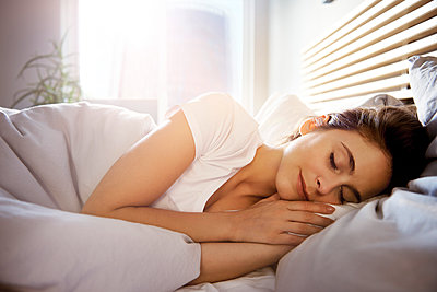 Portrait of young woman sleeping in bed at day - p300m2041673 by gpointstudio