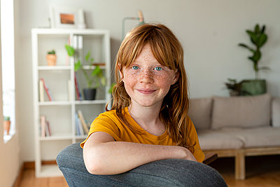 Smiling redhead girl with blue eyes sitting on chair at home - p300m2268053 by Steve Brookland