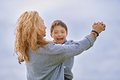 Mother holding hand of son with down syndrome while dancing - p300m2273714 by Arman Zhenikeyev