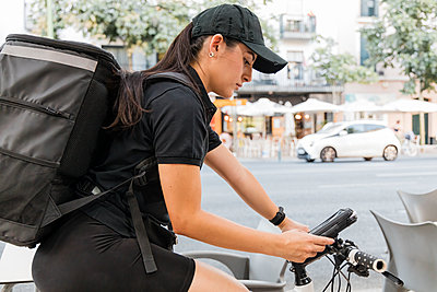 Woman with bicycle working on delivery and courier services, Seville, Spain - p300m2293643 von Julio Rodriguez