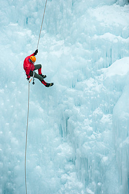 Caucasian man rappelling down ice wall - p555m1479339 by Pete Saloutos
