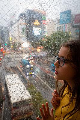 Girl looks through window onto car traffic in the rain - p756m2122764 by Bénédicte Lassalle