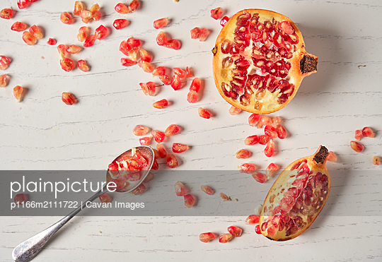 Juicy pomegranate fruit on white wood background. Pomegranate pieces. - p1166m2111722 by Cavan Images