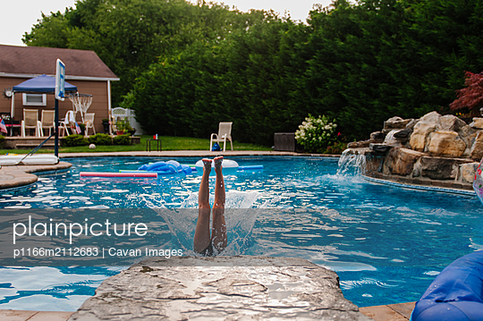 Girl diving into pool half in water with legs and splash - p1166m2112683 by Cavan Images