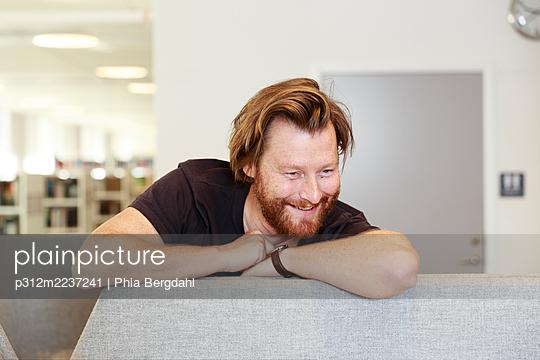 Smiling man looking away - p312m2237241 by Phia Bergdahl