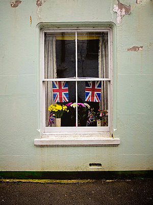 House window with union jack flags and flowers - p1072m829240 by Neville Mountford-Hoare