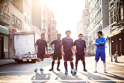 Confident soccer players standing at city street against clear sky - p1166m1098372f by Cavan Images