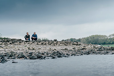 Father and son sitting at the river, talking together - p300m1537332 by Kniel Synnatzschke