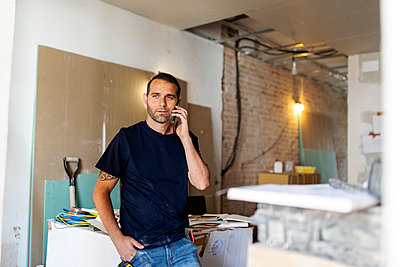 Man on the phone in a house under construction - p300m2207124 by Valentina Barreto