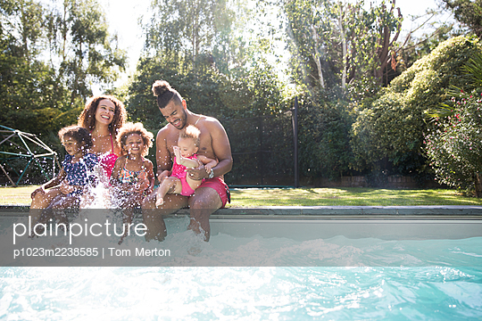 Playful family splashing in sunny summer swimming pool - p1023m2238585 by Tom Merton